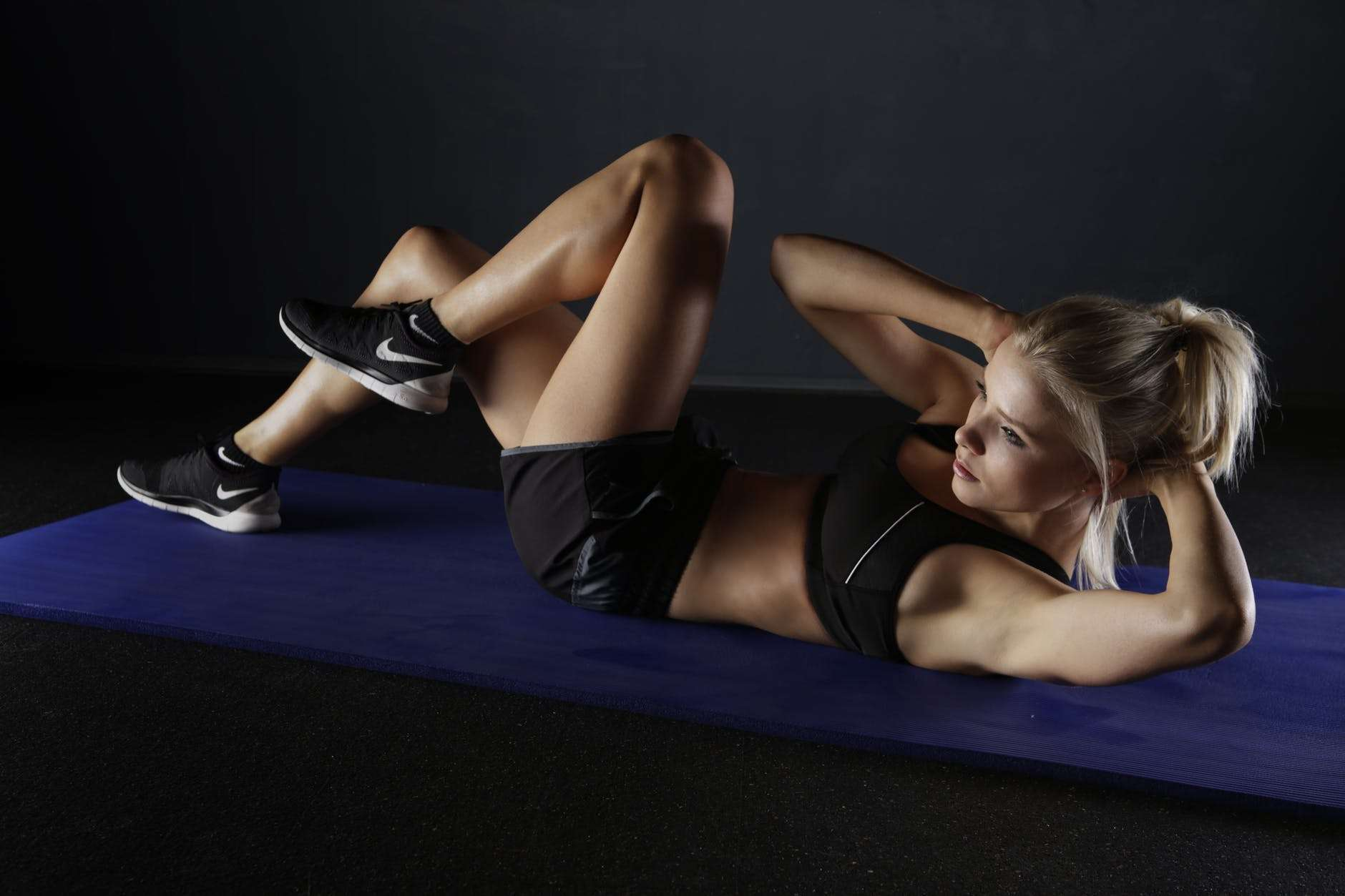 Woman performing partial crunches. These are ideal for those with compromised backs.