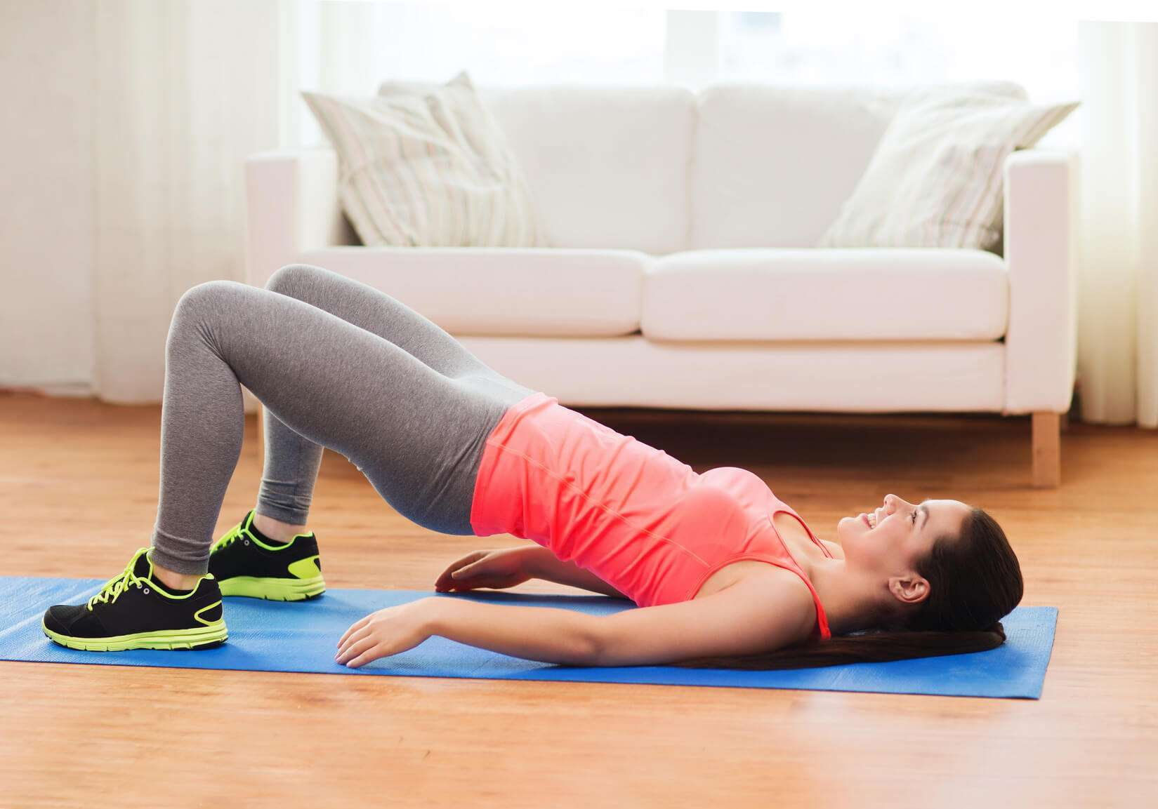 Woman performing bridging, which is an effective exercise for those who suffer from back pain.