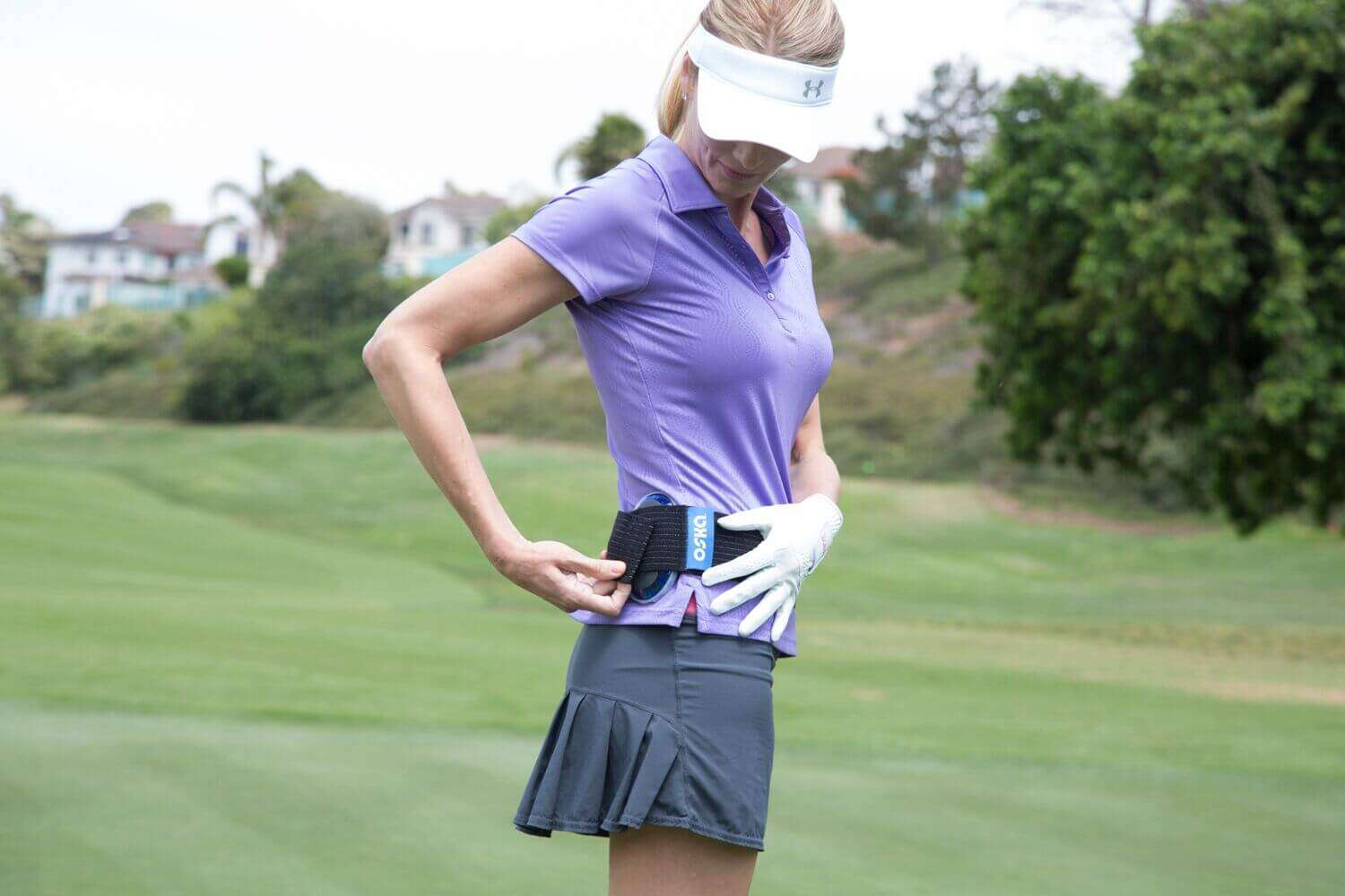Golfer attaching the Oska Pulse while on the golf course.