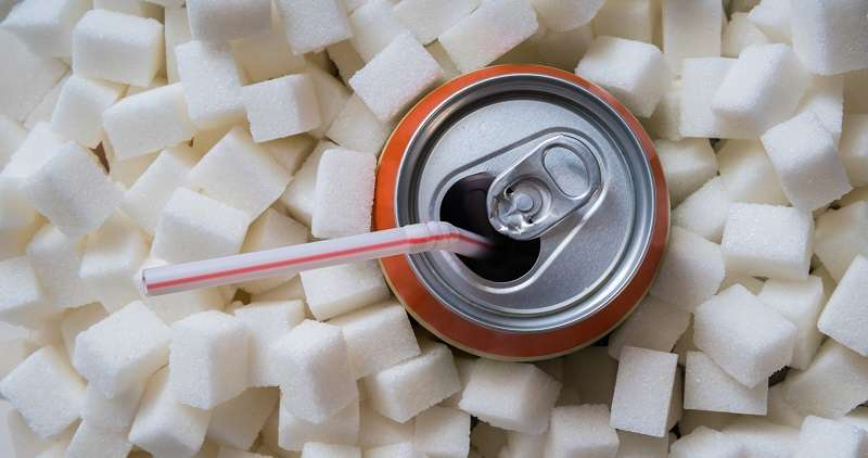 Sugar cubes around a can of soda.