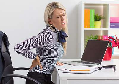 Experiencing lower back pain while at work.